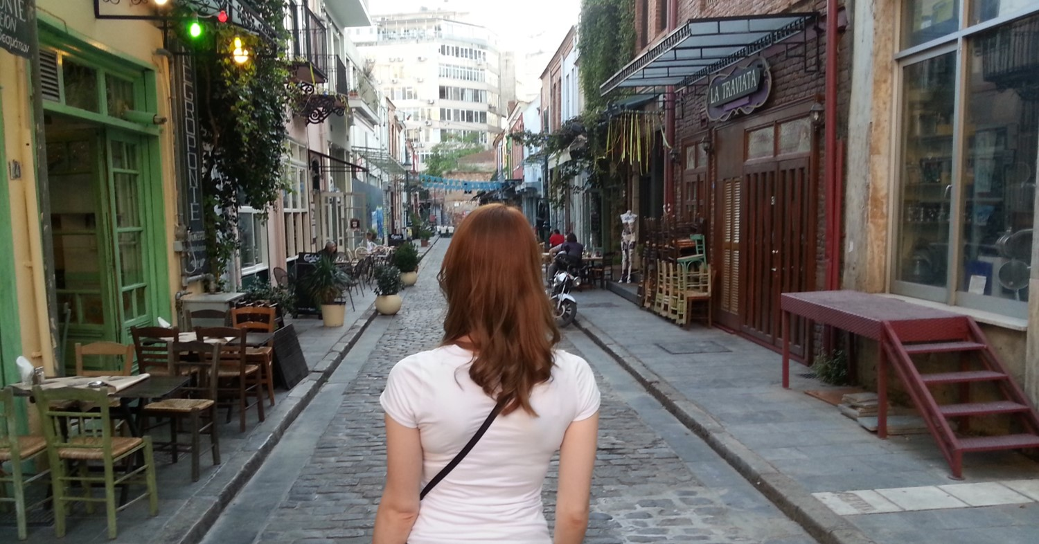 red head woman alone looking down a street
